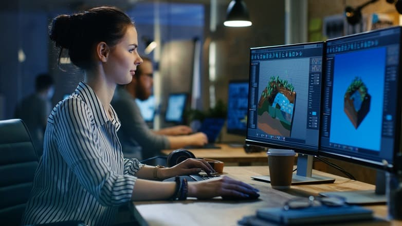 Female Game Developer Works on a Level Design on Her Personal Computer with Two Displays